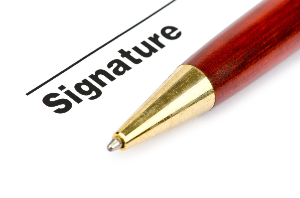 A photo of a signature line with a pen below it.