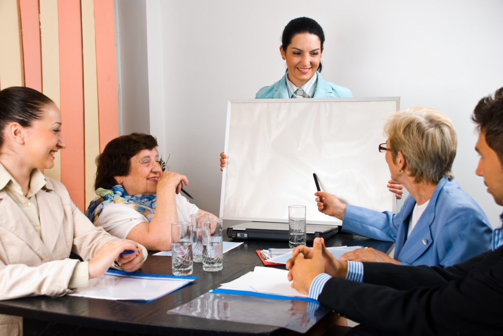 Five people of various ages meeting around a table.  One woman is holding a chart and another is gesturing toward the chart.     <!-- HTML Credit Code for Can Stock Photo --> <a href=