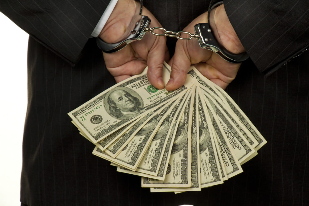 Businessman, handcuffed hands behind his back, holding $100 bills.